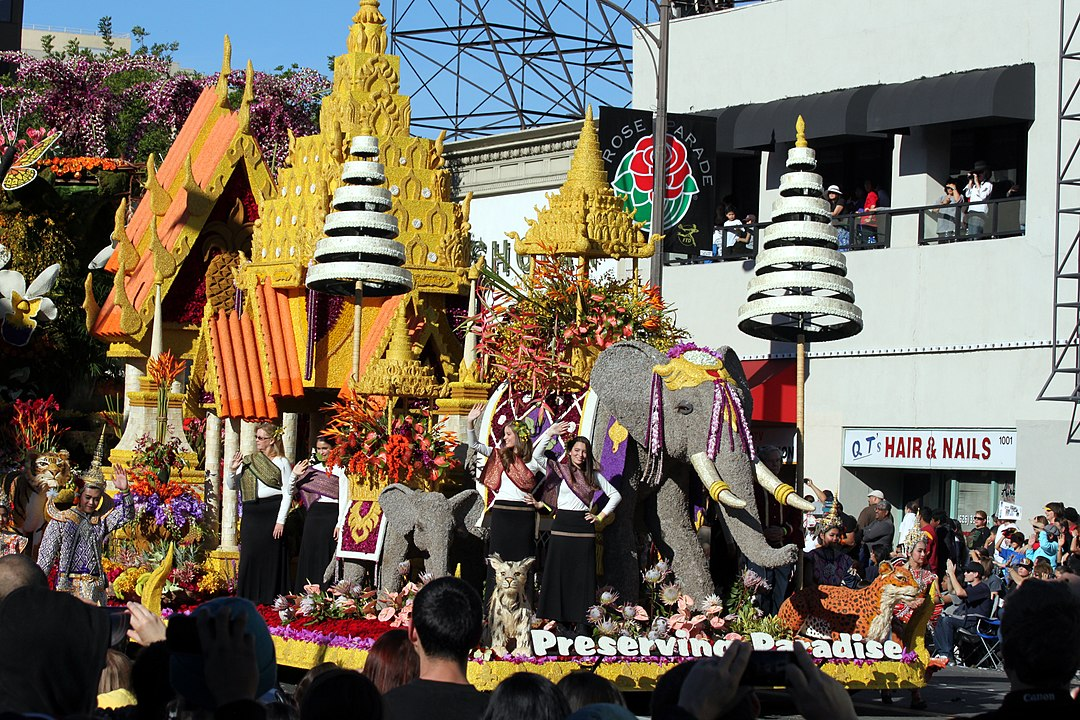 Thailand themed parade with elephant and tiger and waving people